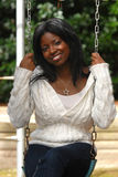 Smiling in the swing. African american woman shows her beautiful smile while sitting in the swing stock photos