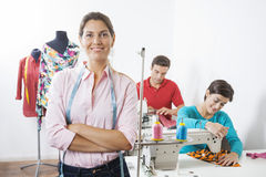 Smiling Tailor With Arms Crossed Standing In Sewing Factory. Portrait of smiling tailor with arms crossed standing at sewing factory with employees working in stock photography