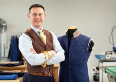 Smiling tailor in his workshop. Portrait of cheerful tailor standing by mannequin with jacket in his workshop Stock Photos