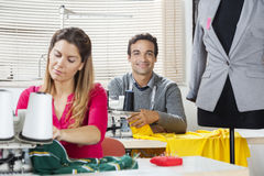 Smiling Tailor Sitting At Workbench In Factory Stock Images