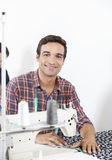 Smiling Tailor Sitting At Workbench In Factory Royalty Free Stock Image