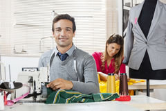 Smiling Tailor Sitting At Workbench In Sewing Factory. Portrait of smiling tailor sitting at workbench in sewing factory with colleague working in background Royalty Free Stock Image