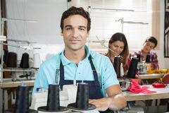 Smiling Tailor Sitting At Workbench In Sewing Factory. Portrait of smiling male tailor sitting at workbench in sewing factory with colleagues in background Royalty Free Stock Images