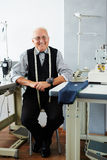 Smiling tailor sitting in workshop Royalty Free Stock Image