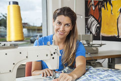Smiling Tailor Stitching Fabric At Workbench. Portrait of smiling female tailor stitching fabric at workbench in sewing factory Royalty Free Stock Image