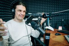 Smiling talking radio presenter in radio studio royalty free stock photography