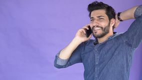 Man talks on phone. Smiling tall and handsome man talking on smartphone, bearded boy having a pleasant chat on phone, isolated shot in the purple background stock video footage