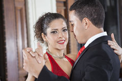 Smiling Tango Dancer Performing Gentle Embrace Step With Man. Portrait of smiling female tango dancer performing gentle embrace step with men in restaurant Royalty Free Stock Photography