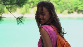 Smiling tanned brunette woman standing at mountain lake and enjoying fresh clear air