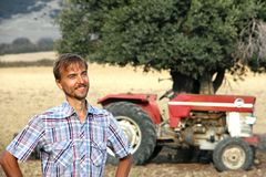 Smiling tanned farmer stands near the old tractor in the middle of a plowed field. Countryside in Cyprus royalty free stock photo