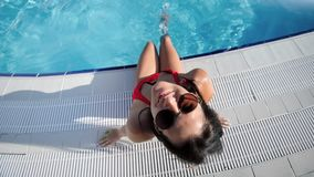 Smiling tanned girl in bikini enjoying vacation swimming pool having fun looking at camera