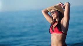 Smiling tanned woman in bikini wearing hat having fun at sunset seascape medium shot