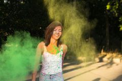 Smiling tanned woman with short hair posing with exploding Holi Royalty Free Stock Images