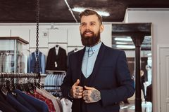 Smiling tattoed male with stylish beard and hair dressed in elegant suit standing in menswear store. Smiling tattoed male with stylish beard and hair dressed in royalty free stock photography