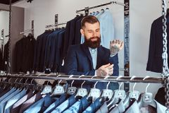 Smiling tattoed male with stylish beard and hair dressed in elegant suit standing in a menswear store. Smiling tattoed male with stylish beard and hair dressed royalty free stock photos