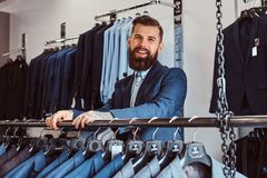 Smiling tattoed male with stylish beard and hair dressed in elegant suit standing in a menswear store. Smiling tattoed male with stylish beard and hair dressed stock photo