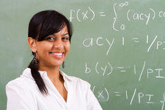 Smiling teacher. Young beautiful smiling indian female teacher in front of chalkboard Royalty Free Stock Photos