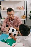 smiling teacher and african american preschooler holding soccer ball together stock photo
