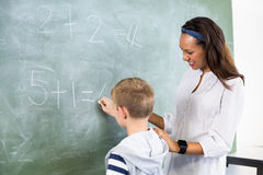 Smiling teacher assisting boy in doing addition on chalkboard. In classroom at school stock images