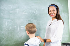 Smiling teacher assisting boy in doing addition on chalkboard. In classroom at school Stock Photos