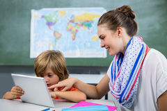 Smiling teacher assisting boy using digital tablet. In classroom Royalty Free Stock Photography