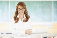 Smiling teacher in the classroom. Shot of a smiling female teacher standing in the classroom with chalboard in the background Stock Photos