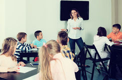 Smiling  teacher and elementary age kids drawing. At classroom Royalty Free Stock Photography