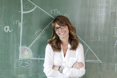 Smiling teacher in front of the blackboard. Smiling teacher standing in front of the  blackboard Royalty Free Stock Images