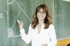 Smiling teacher in front of the blackboard Stock Photo
