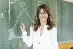 Smiling teacher in front of the blackboard Stock Photography