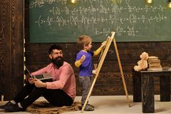 Smiling teacher in glasses looks at kid wiping chalkboard. Father and excited blond kid learning math. Side view boy and. Men sitting on floor with laptop royalty free stock images