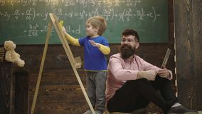 Smiling teacher in glasses looks at kid wiping chalkboard. Father and excited blond kid learning math. Side view boy and. Man sitting on floor with laptop. Boy stock footage