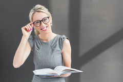 Smiling teacher with glasses standing in front of blackboard and holding book Royalty Free Stock Photos