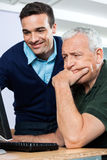 Smiling Teacher Helping Senior Man In Using Computer Royalty Free Stock Photos