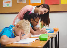 Smiling teacher helping a student Stock Image