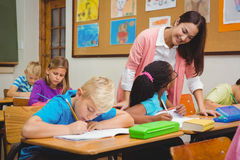 Smiling teacher helping a student Royalty Free Stock Photos