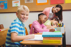 Smiling teacher helping a student Royalty Free Stock Images