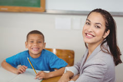 Smiling teacher and her pupil sitting at desk. Portrait of smiling teacher and her pupil sitting at desk in a classroom Stock Photo