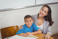 Smiling teacher and her pupil sitting at desk. Portrait of smiling teacher and her pupil sitting at desk in a classroom Stock Image