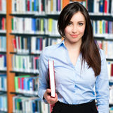 Smiling teacher holding a book in a library Royalty Free Stock Photos
