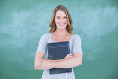 Smiling teacher holding notebook in front of blackboard Stock Images