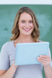 Smiling teacher holding tablet pc. In front of blackboard stock photography
