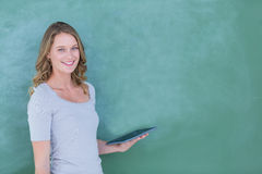 Smiling teacher holding tablet pc. In front of blackboard royalty free stock photo