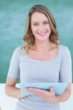 Smiling teacher holding tablet pc in front of blackboard stock images