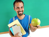 Smiling teacher hugging books and holding an apple. Stock Photography
