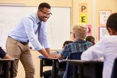 Smiling teacher leaning on elementary school pupil�s desk Stock Images