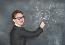 Smiling teacher painting a happy sun royalty free stock photos