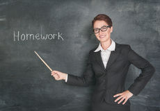 Smiling teacher with pointer and phrase Homework. On blackboard chalkboard Stock Image