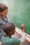 A smiling teacher and a pupil making an addition Royalty Free Stock Photo