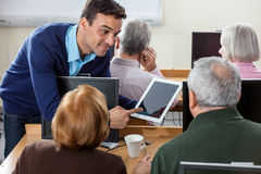 Smiling Teacher Showing Digital Tablet To Senior Students In Cla. Smiling male teacher showing something on digital tablet to senior students at desk in computer Stock Photo
